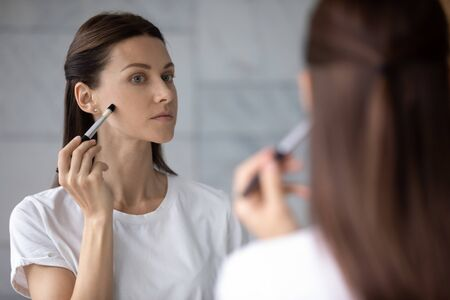 Over shoulder view serious pretty 35s woman reflected in mirror hold brush applying make up foundation concealer cream on perfect fresh skin. Grooming, morning routine, makeup, skincare beauty concept