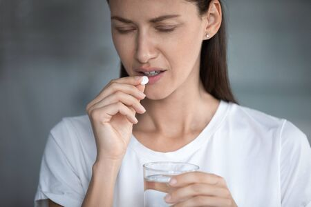 Close up image of unhealthy 35s female closed eyes suffers from migraine or hangover holds glass of water takes painkiller pill for throbbing headache reducing, medical abortion hard decision concept