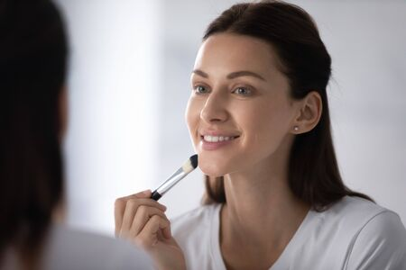 Close up beautiful young woman reflected in mirror smile applying concealer foundation cream using natural bristle make-up professional brush, facial makeup, cosmetics tool, beauty, skincare concept