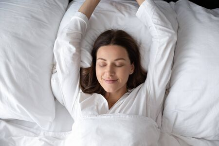 Top view young woman with closed eyes lying in pyjamas raising stretching arms wake up feels rested after enough night sleep, early morning, natural beauty, fresh girl at home, hotel bedroom concept Stok Fotoğraf