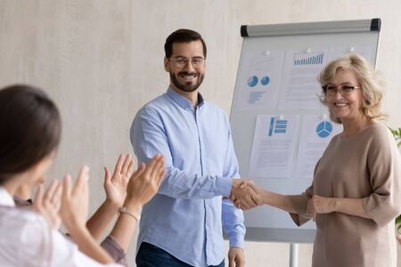 Happy 60 year old businesswoman congratulation hand shaking young businessman after success flipchart presentation new project in boardroom at meeting. Mature manager shaking hand good employee.