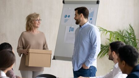 Young businessman on behalf of company welcoming 60 year old businesswoman holding box at meeting. Introducing hired worker in office getting acquainted supporting new team member on first work day. Stockfoto