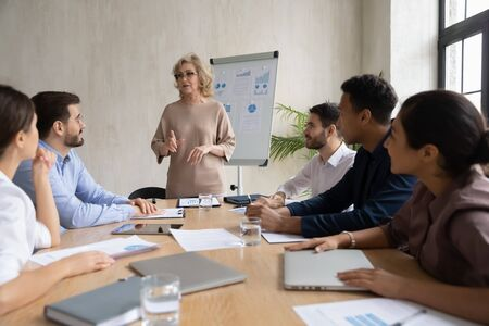 Serious mature 60 year old businesswoman talking, presentation new project in boardroom at company meeting. Adult confident woman coach auditor speaks about business on flip chart graphs background.