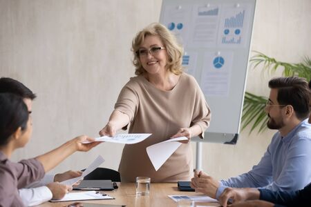 Happy executive mature 60 year old businesswoman gives handout in boardroom at meeting. Smiling female coach lead new project presentation for colleagues with flipchart, conversation at negotiation.