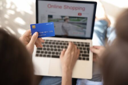 Close up top view of young people shopping online on laptop make payment with credit card, couple buyers pay on internet banking service system, buy or purchase on web from home, ecommerce concept