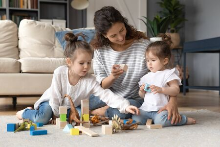 Loving young Caucasian mother sit on floor in living room playing building bricks with little daughters, caring mom or nanny construct with wooden block with small girls children at home together