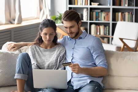 Young Caucasian couple sit relax on couch in living room shopping online on laptop paying with credit card, millennial man and woman make internet payment, buying on web using computer