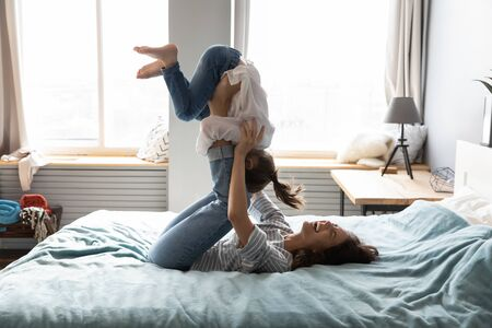 Smiling young Caucasian mom lying on comfortable bed have fun engaged in funny game activity with small daughter, overjoyed mother and little girl child playing together in cozy bedroom at home Фото со стока