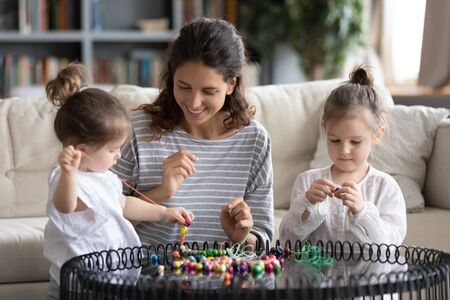 Smiling young Caucasian mom have string thread wooden beads with little preschooler daughters, happy mother or nanny make bracelets engaged in creative activity with small girls children at home Banco de Imagens