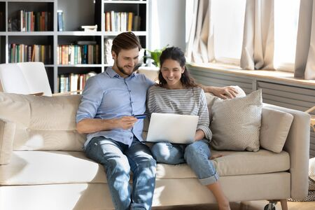 Smiling young Caucasian couple sit on sofa at home shopping online using laptop enter credit card details, happy man and woman make payment with internet banking system, buy on web from home Фото со стока
