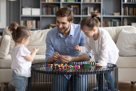 Loving young Caucasian father engaged in funny creative activity making bracelets with little daughters, happy dad have fun string thread wooden colorful beads play with small girls children Banco de Imagens