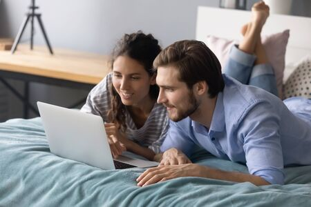 Happy young man and woman relax lying in cozy bed browsing fast wireless internet shopping on laptop together, millennial Caucasian couple rest in bedroom watch video using modern computer at home
