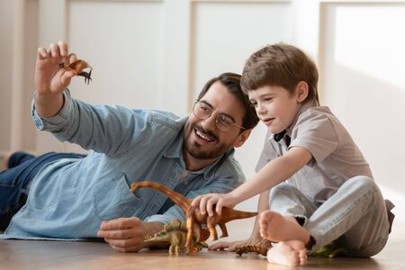 Smiling young Caucasian father and little preschooler son sit on warm floor at home play with rubber dinosaur figures together, playful dad and small boy child have fun engaged in game at home Banco de Imagens