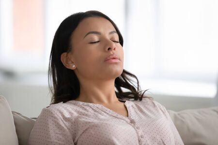 Close up calm African female rest leaned on couch in modern living room, closed eyes breath fresh humidified air. Fatigue relief repose, boost inner balance and mindfulness, meditation process concept Banque d'images