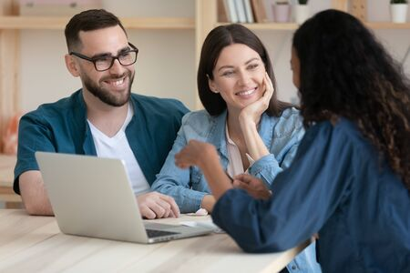Real estate agent consulting happy young couple about buying house rent purchase mortgage in office at meeting. Smiling millennial family clients listening financial advisor using laptop.