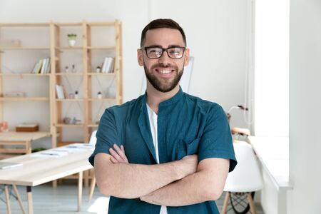 Close up head shot portrait picture of happy businessman crossing hands looking at camera. Smiling confident millennial man manager with glasses on workplace background in office.