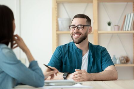 Close up happy bearded man applicant makes good first impression for female hr manager in office. Board smiling male job seeker introduces himself for businesswoman mentor to job at hire meeting.