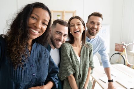 Close up headshot portrait picture of diverse team taking selfie looking at camera. Happy confident millennial african amerucan woman manager with colleagues on workplace background in office. Banque d'images