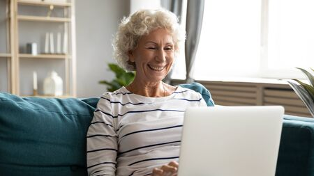 Happy hoary middle aged grandmother sitting on sofa, looking at laptop screen. Smiling grey haired mature woman reading pleasant news, chatting with friends in social network, watching funny movie.