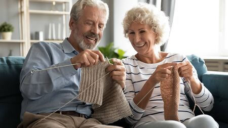 Laughing positive mature senior married family couple sitting on cozy couch, knitting handmade warm sweaters scarfs with woolen threads. Happy older grandparents enjoying hobby activity at home.