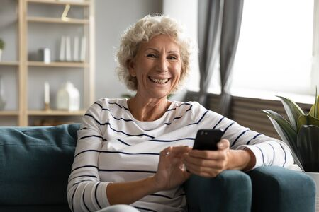 Smiling positive middle aged grey haired woman holding smartphone in hands, relaxing on comfortable sofa at home. Happy senior mature grandmother with cell phone looking at camera, enjoying free time.