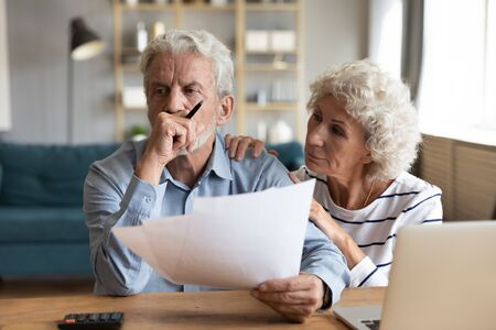 Compassionate elderly woman supporting upset stressed mature husband, received bad news banking letter. Unhappy depressed family married couple having financial trouble, got house eviction notice.