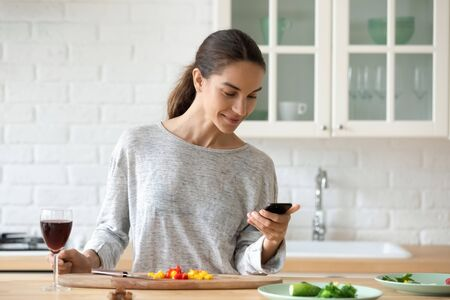 Smiling millennial girl stand at kitchen counter cooking drinking wine texting messaging on modern cellphone, happy young woman preparing food with Internet recipe on cellphone gadget in home kitchen
