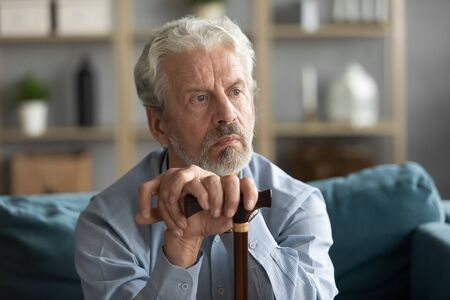 Head shot pondering hoary elder senior man leaning on wooden walking stick, resting on comfortable sofa. Upset middle aged mature grandfather thinking of disability, health problems or difficulties.