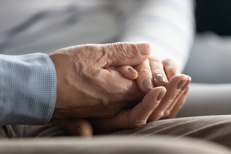 Close up middle aged woman holding wrinkled hand of retired husband, showing love care. Affectionate senior old family couple supporting each other, making peace at home, reconciliation concept.