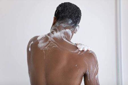 Back view of young african american man stand in bathroom wash foam body with natural foamy gel, biracial male take morning daily shower in home bath, get ready, personal hygiene, skincare concept