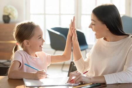 Overjoyed young mom and small daughter give high five celebrate success studying or painting at home together, happy mother or nanny cheering smiling little girl child when drawing, education concept Banco de Imagens