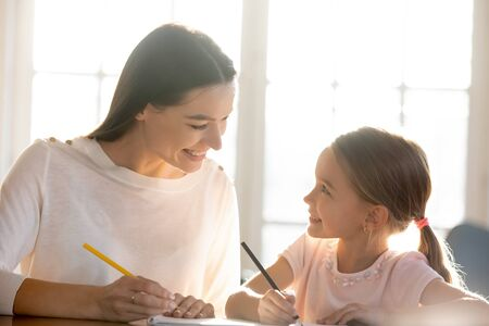 Loving young mother sit at desk studying together with little happy daughter, smiling mom or nanny help teach small girl child, drawing or painting, have fun on weekend at home, education concept Banco de Imagens