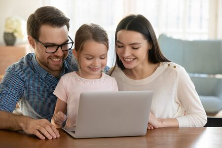 Overjoyed young family with little daughter sit at table watch funny video on laptop together, smiling mom and dad have fun with small girl child using modern computer browsing internet at home