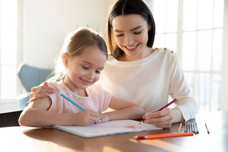 Caring young mom and small preschooler daughter have fun painting with colorful pencils together, smiling mother or nanny relax drawing with little girl child, enjoy leisure family weekend at home Banco de Imagens