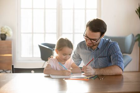 Loving young father sit at desk studying drawing with small preschooler daughter, caring happy dad have fun painting picture with little girl child, enjoy leisure family weekend at home together