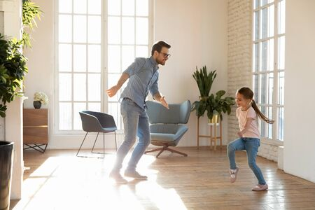 Loving playful young father have fun dance together with excited preschooler daughter in living room, happy dad engaged in funny activity entertain with little girl child, relax on weekend at home Banco de Imagens