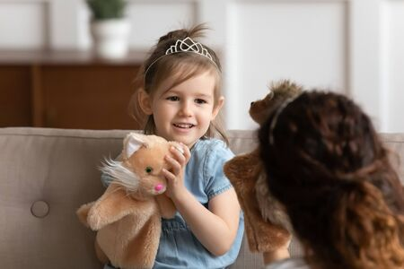 Cute little girl wearing princess diadem and loving mother playing dolls theatre together close up, holding fluffy animals toys in hands, sitting on cozy couch in living room, enjoying leisure time