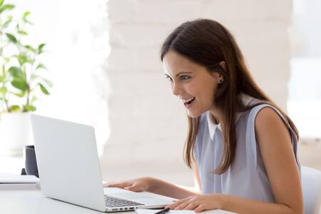 Surprised millennial female employee look at laptop screen stunned by unexpected work result, amazed woman worker shocked by unbelievable email or message on computer at workplace, luck concept Stockfoto