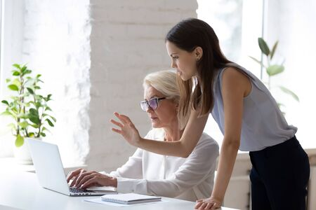 Successful young businesswoman manage supervise middle-aged female employee working on laptop in office, confident millennial female employer help assist senior intern with computer job at workplace