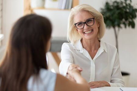 Smiling middle-aged businesswoman shake hand get acquainted greeting with female applicant, happy senior woman boss handshake candidate or business partner after successful interview or meeting