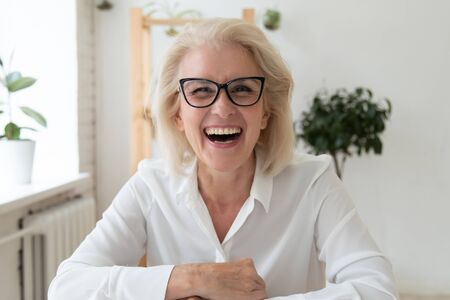 Headshot portrait of excited mature businesswoman in glasses have fun laugh talking on video call, overjoyed happy middle-aged woman employee smile joke speaking online on WebCam conference