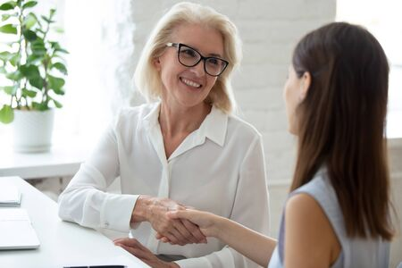 Happy middle-aged businesswoman shake hand of young woman candidate get acquainted greeting at meeting, smiling senior female CEO or boss handshake girl applicant after successful interview in office