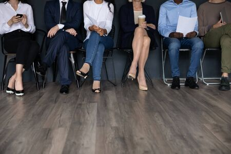 Diverse people sitting on chairs in row, six female and male applicants candidates waiting for job interview, holding resume documents, using gadgets, human resources and employment concept