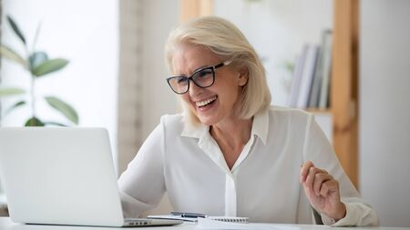 Overjoyed middle-aged businesswoman in glasses sit at desk in office read great news online on laptop, happy mature female employee feel excited with email or message on computer, success concept
