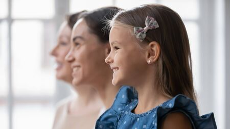 Close up profile view of smiling three generations of women look in distance bright future dreaming or visualizing together, happy girl with young mom and mature grandmother show unity, bonding