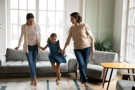 Happy three generations of women have fun dancing holding hands together in living room, overjoyed little girl with young mom and senior grandmother feel energetic active relaxing on weekend at home