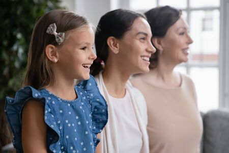 Profile view of overjoyed three generations of women look in distance smiling visualizing together, happy little girl with young mom and senior grandmother pose for picture at home, unity concept Banque d'images