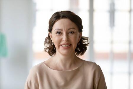 Portrait d'une femme caucasienne mature souriante montrant de l'optimisme et de la bonne humeur, une femme heureuse d'âge moyen regarde la caméra posant à la maison, parle par appel vidéo ou a une conversation webcam en ligne