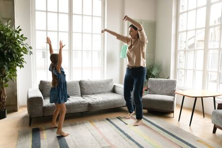 Happy energetic middle-aged 60s grandmother have fun dancing with little preschooler granddaughter at home, smiling senior granny enjoy active entertaining family weekend with small grandchild