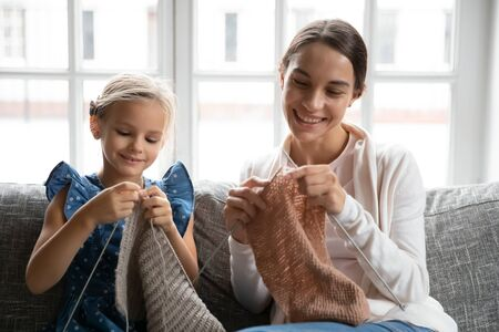 Smiling young Caucasian mom sit on sofa knit with needles with cute little preschooler daughter, happy mother or nanny engaged in hobby activity, improve motor skills with small girl child at home